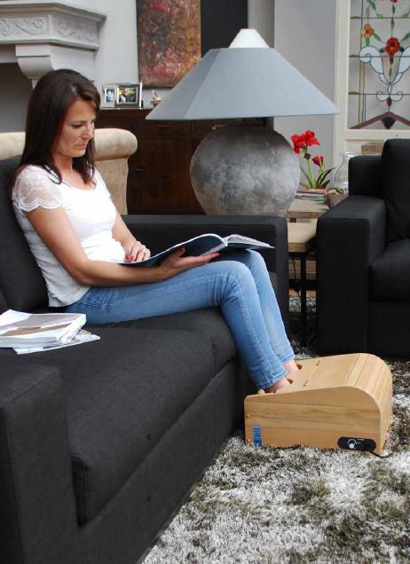 een jonge vrouw zit met haar voeten in een Health Mate Voetensauna