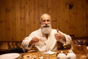 Oudere man met witte baard en snor in een witte badjas geniet van een tas thee.