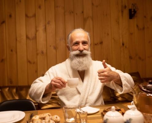 Een man met een mooie witte baard geniet in zijn witte badjas na een heerlijke sauna beurt ter verlichting van zijn artrose pijn.
