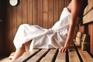 een vrouw zit in een sauna met een handdoek om
