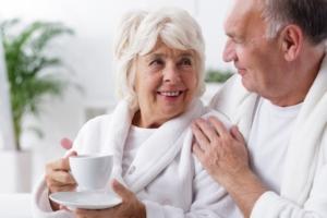 Ouder koppel in een witte badjas genieten samen van een kopje thee of koffie.