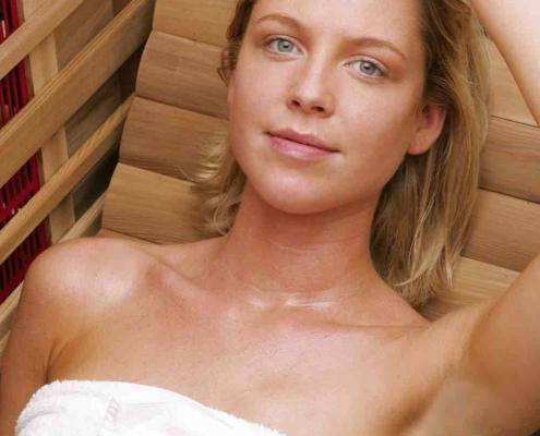 Een jonge vrouw ontspant in een Health Mate infrarood sauna