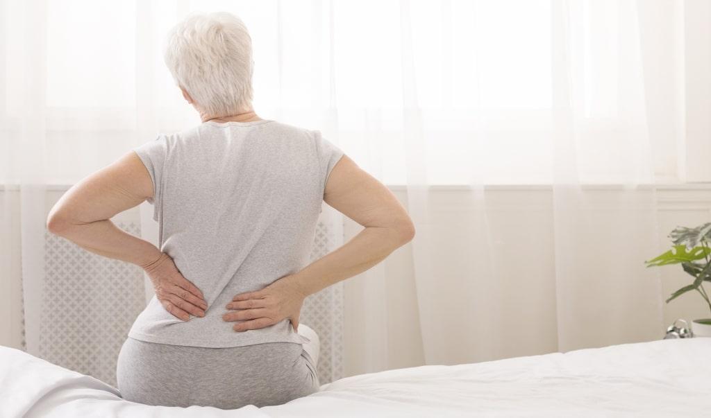 Vrouw zit op het bed en heeft lage rugpijn